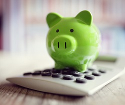 Green piggybank on calculator